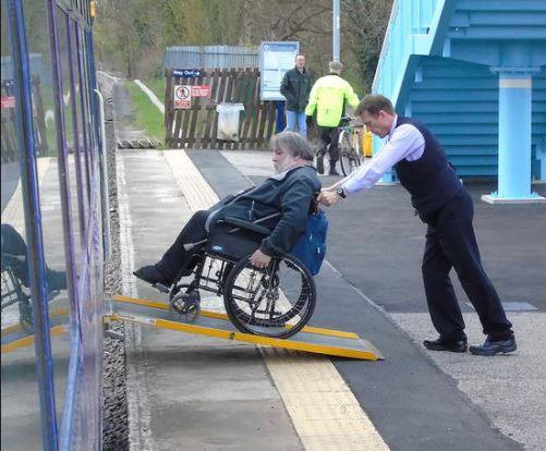 Station assistant helps man in wheelchair onto train