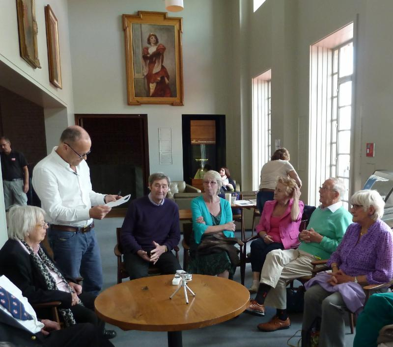 Dementia research group with man standing up and reading