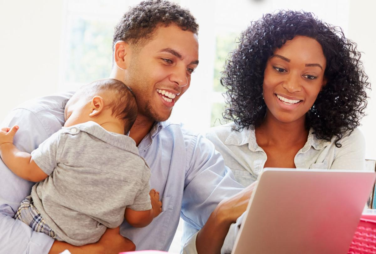 a couple at their computer, the father is holding a baby