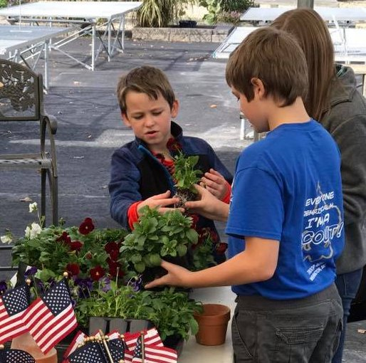 Kids planting fall planters to give to veterans