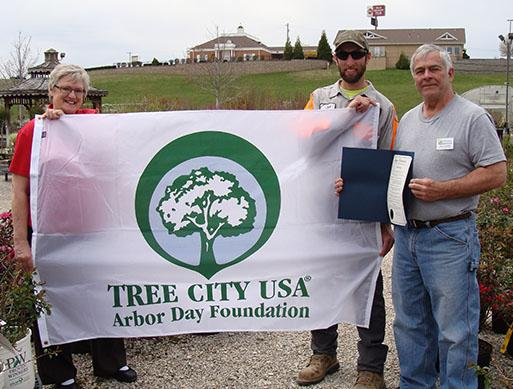 Representatives including Sandi with Hillermann Nursery and Florist - Josh with the City of Washington and John with Washington in bloom hold the banner the city received for the Tree City USA status from the Arbor Day Foundation - picture 4-21-18