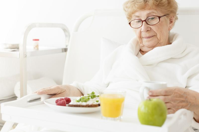 Elder eating healthy meal at hospital which consists of an apple and orange juice