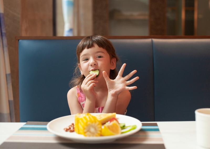 The concept of feeding a child on a journey. Girl eating vegetables.
