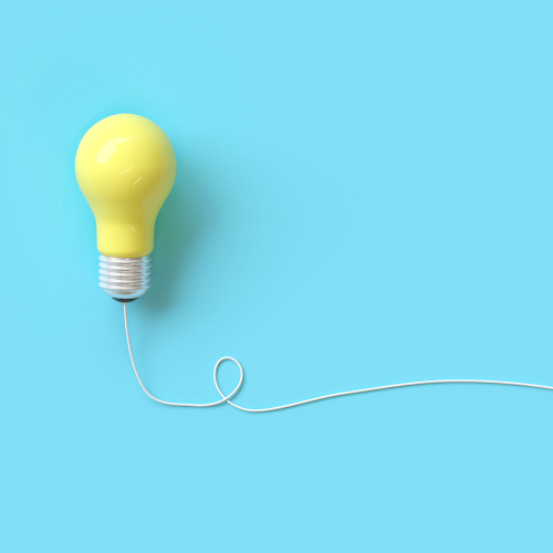 Yellow lightbulb with wire on blue background for copyspace. minimal idea concept. top view
