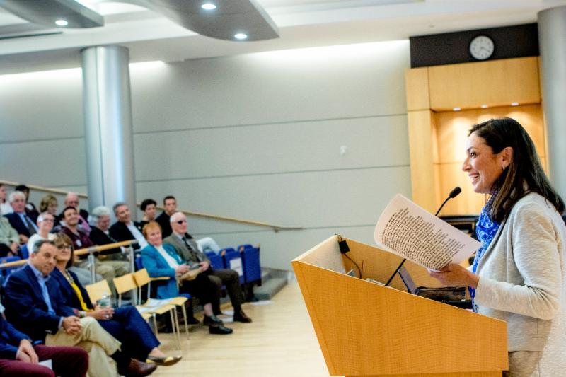 A woman at the podium on the right addressing an auditorium of people