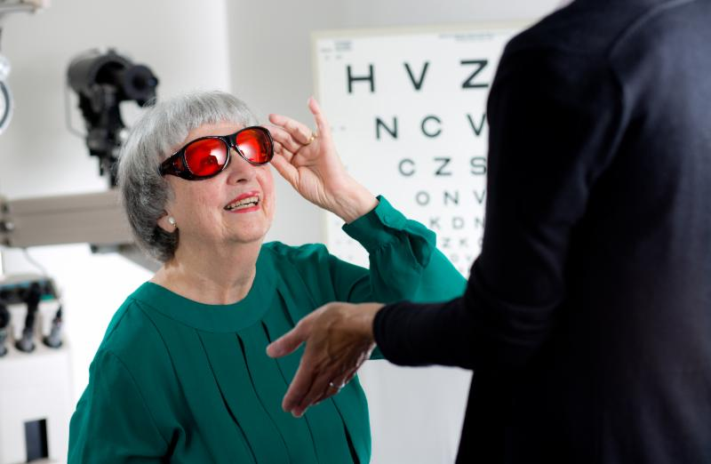 A woman tries on glasses at a low vision exam