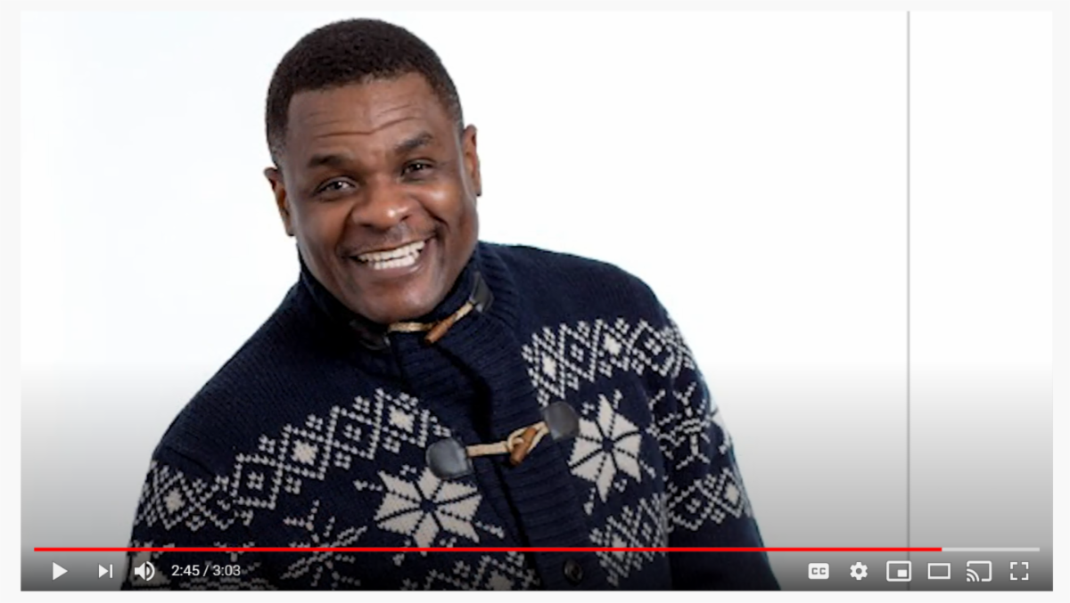 YouTube Screenshot of a smiling haitian man wearing a patterned sweater