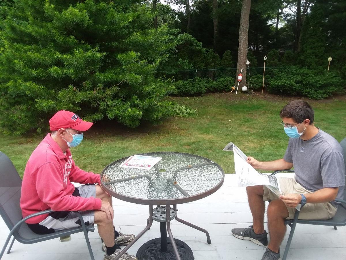 A gentleman wearing a pink sweatshirt and a mask sitting at a patio table facing a man in a mask reading a newspaper to him