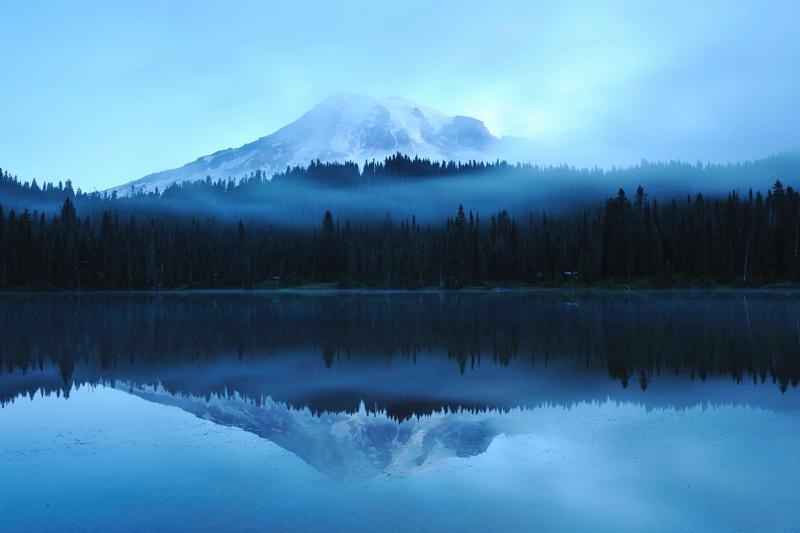 A landscape photo of a mountain surrounded by trees and reflected in a body of water below