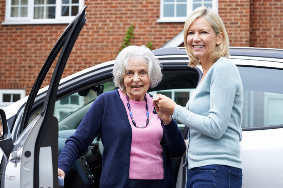 an older woman being assisted out of her car by another woman