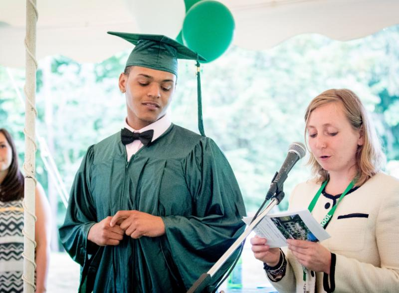 Ivy Street student on the left receiving his diploma from a faculty member on right