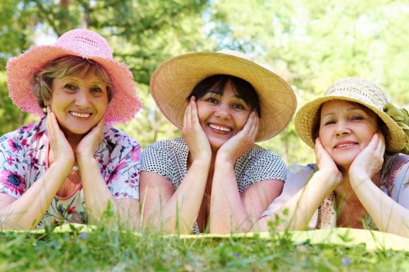 three_women_hats_grass.jpg
