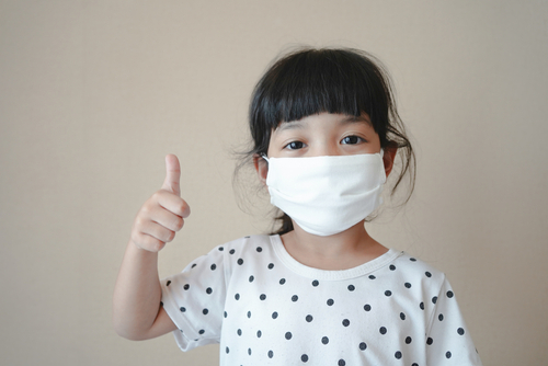 Asian kid use medical mask or surgical mask to protect her from virus_ sickness_ Covit-19 and coronavirus infection.