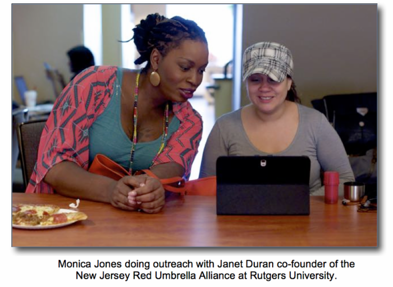 Two women sitting at a table (Monica Jones doing outreach with Janet Duran co-founder of the New Jersey Red Umbrella Alliance at Rutgers University).