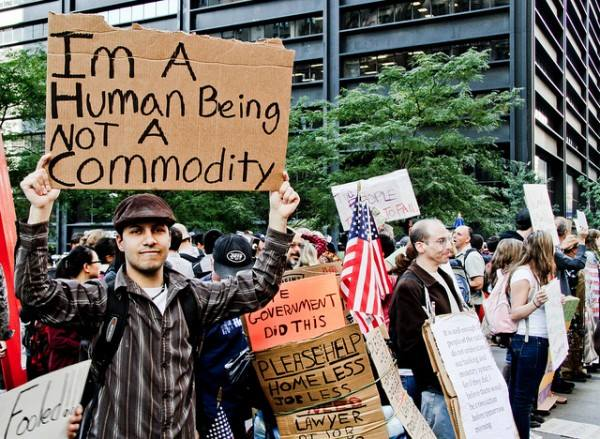 "Man holding a sign that reads: ""I'm a human being not a commodity."""