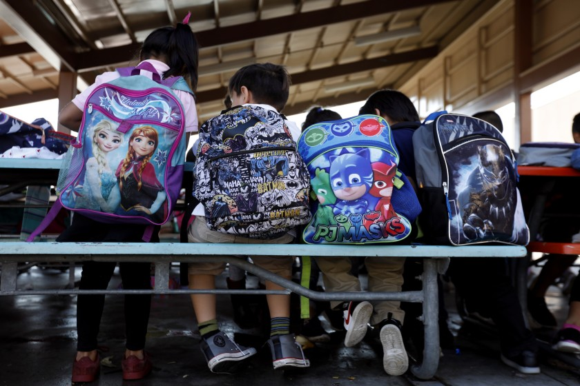 four kids with backpacks sitting at picnic table