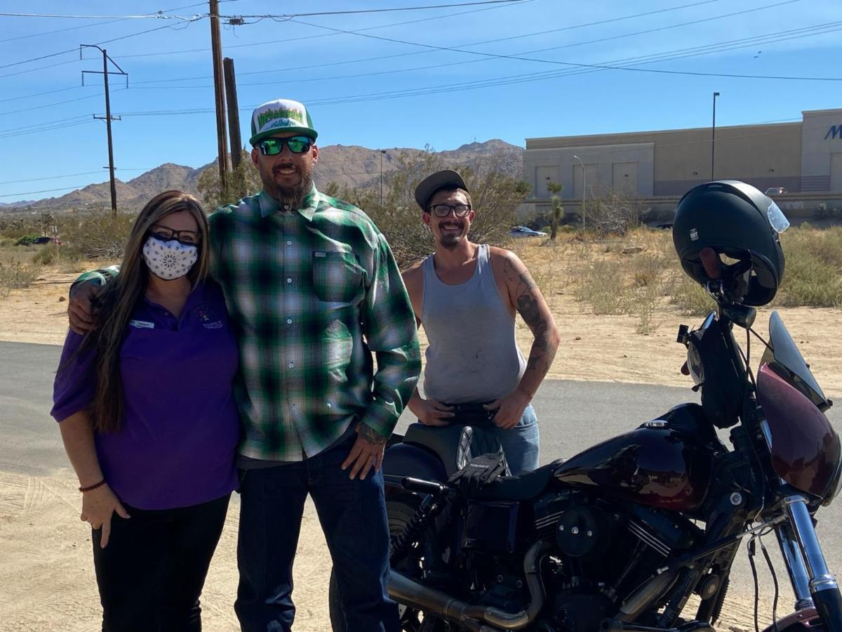 three people standing near motorcycle