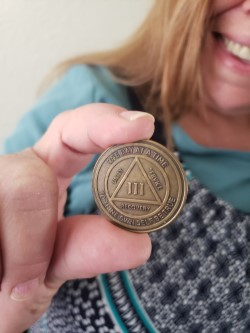 person holding sobriety coin
