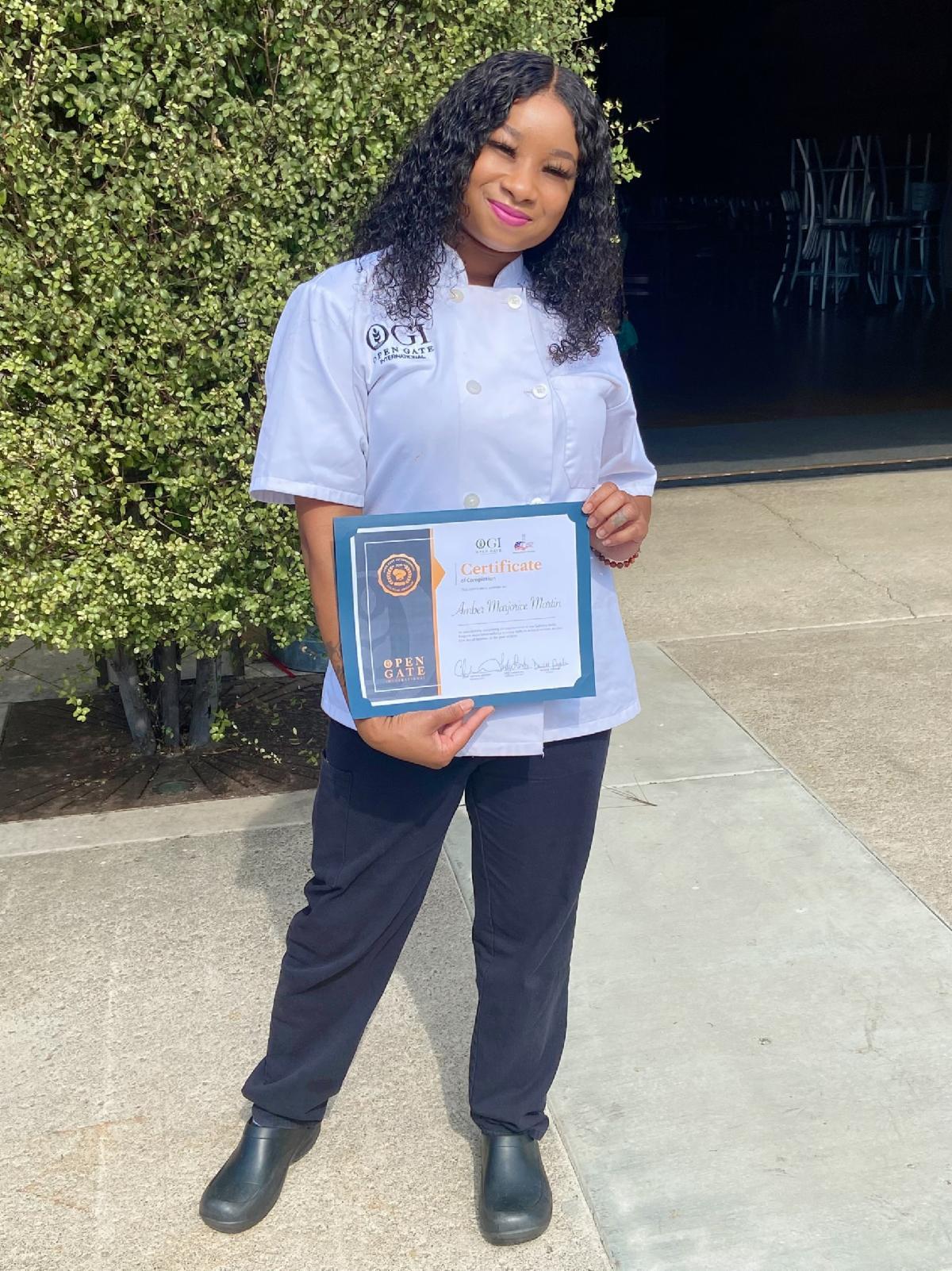 graduate holding her certificate