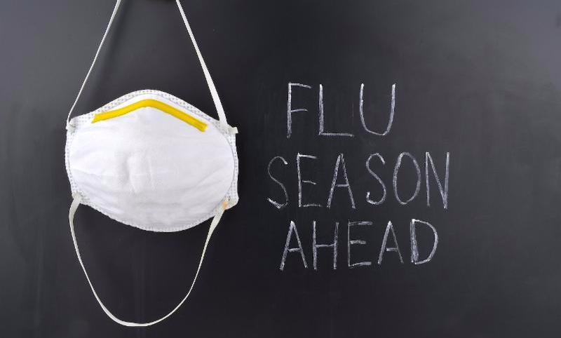 Chalkboard with Flu Season Ahead and mask on it