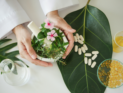 scientist or doctor making herbal medicine with herb leaves _ capsule_ tablets. hands.top view.