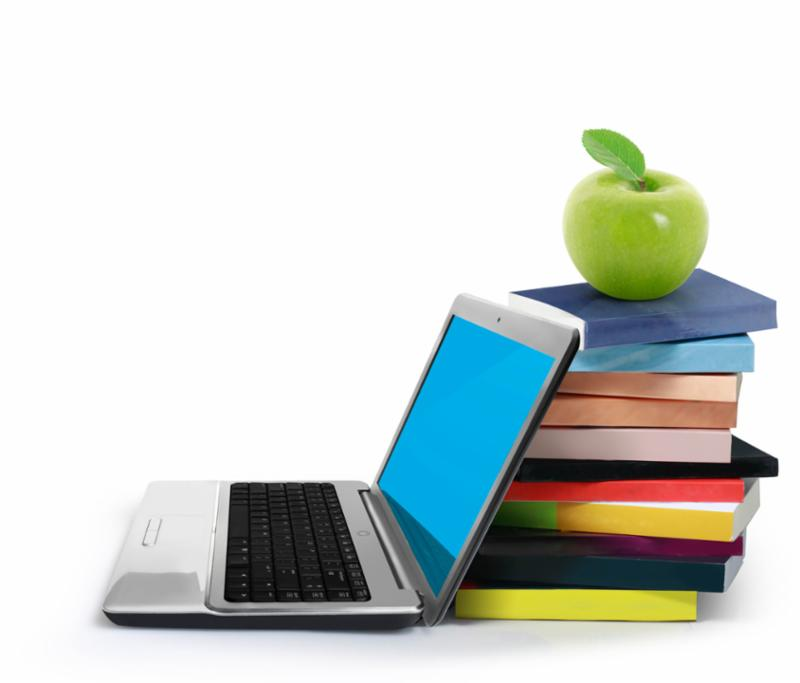 an open laptop computer next to a stack of colorful books with a green apple on top of the pile