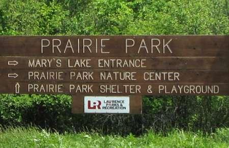 large wooden sign at the entrance to Prairie Park Nature Center reading prairie park and mary's lake