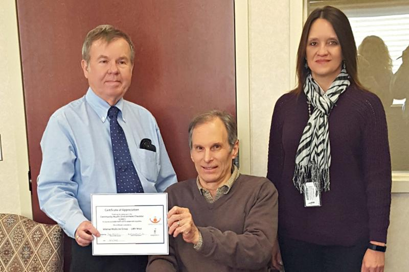 Bob Mikesic presenting CHEC certificate of appreciate to Dr. Gregory Schnose and Emily Herman