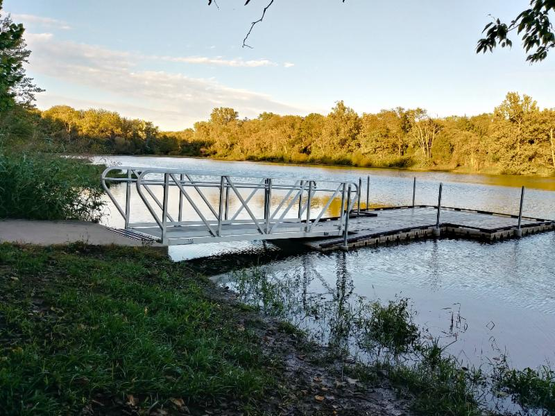 Fishing dock at lake with trees in background