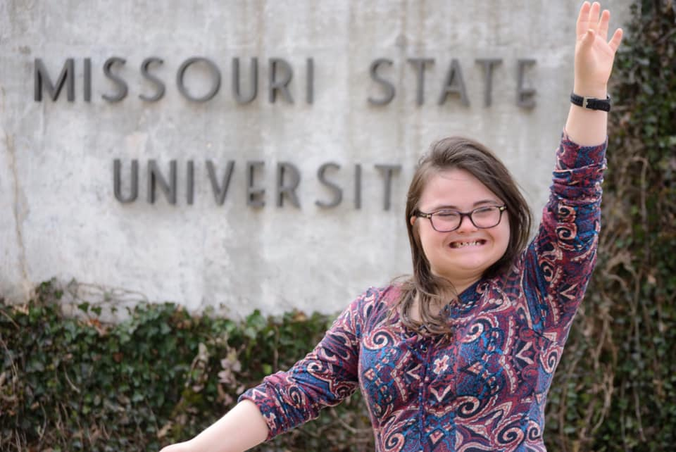 female college student with down syndrome smiling and posing in front of Missouri State University sign