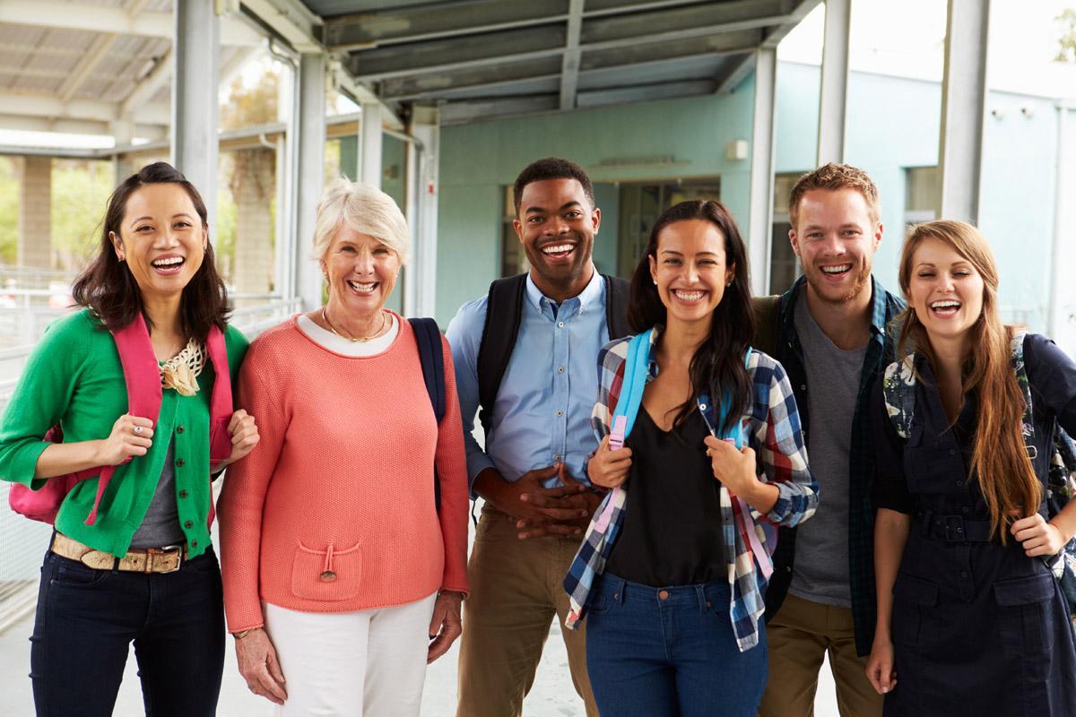 group of smiling teachers wearing backpacks