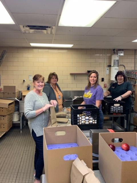 District staff packing lunches in school_s kitchen
