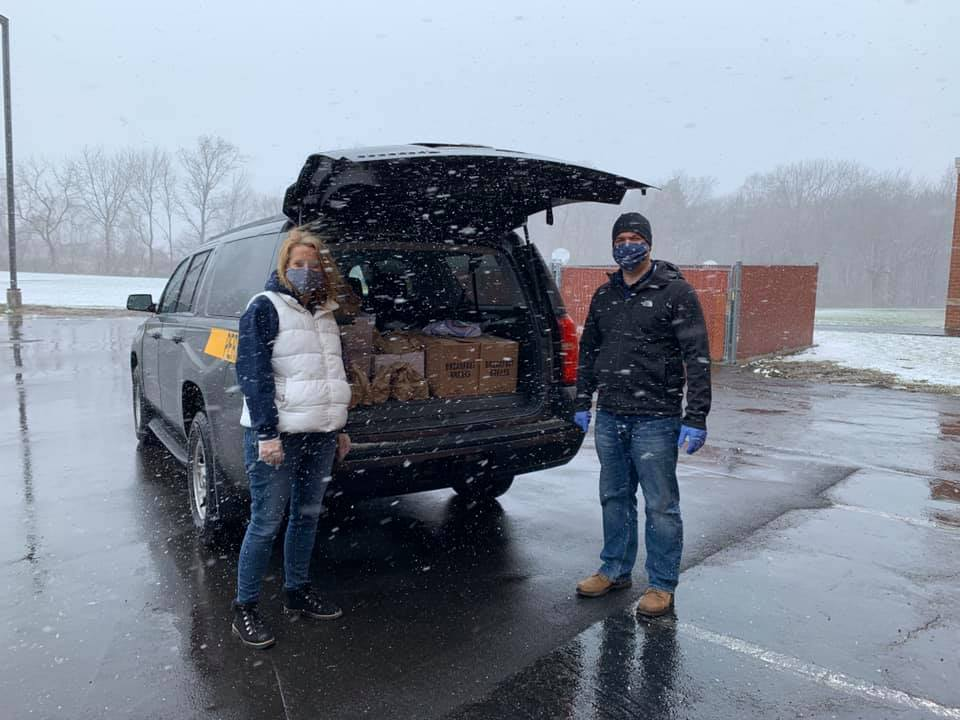 District staff packing school van with lunches for families