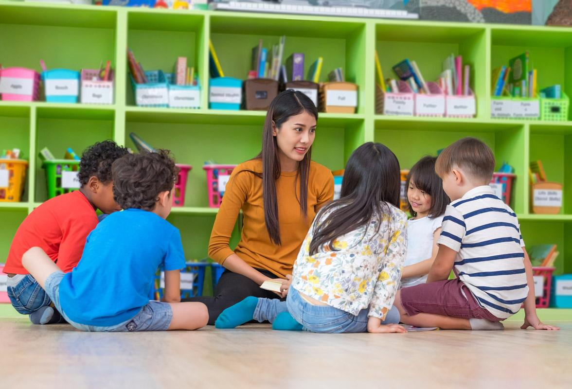 teacher with young students in circle on classroom floor