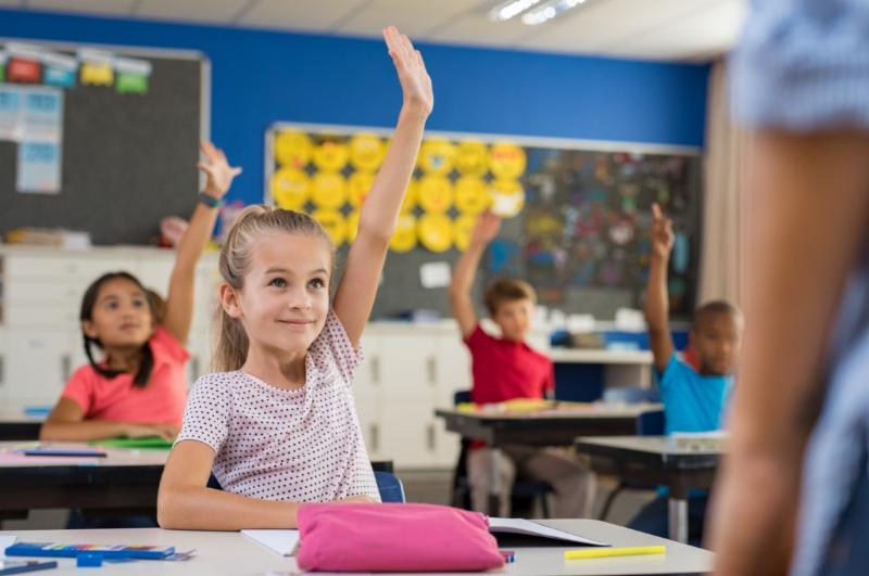 students at desks in classroom raising their hands