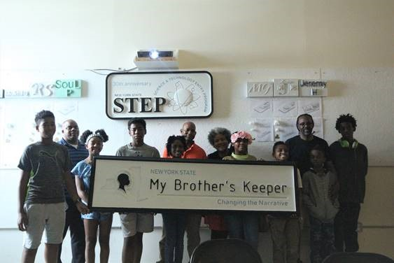 STEP students holding the MBK sign they recently created in front of the STEP sign they previously made.