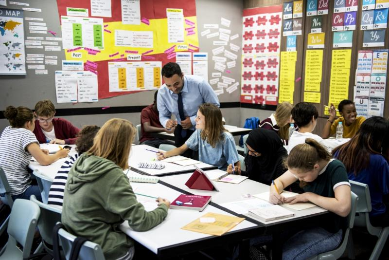 teacher in classroom with high school students working in groups at tables