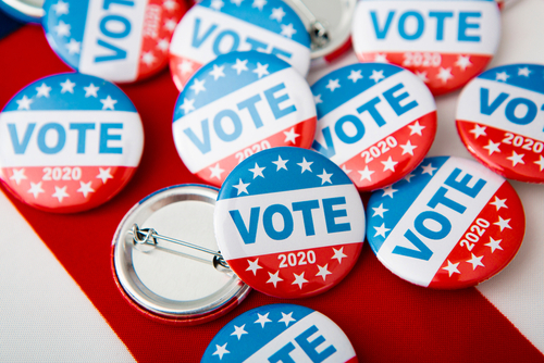 Election 2020 in the USA. Variety Of Presidential Election Buttons on American flag