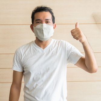 A man wearing mask for prevent the spread of the Covid-19 and posing thumb up with confidence_ Covid-19 virus protection concept in Thailand.