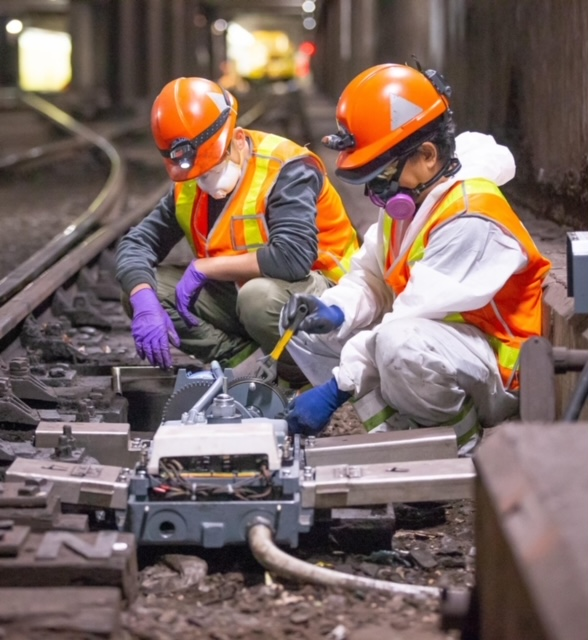 two TTC employees working on a signal at track level