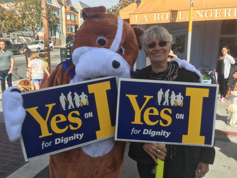 dignity dog and friend with Prop I signs