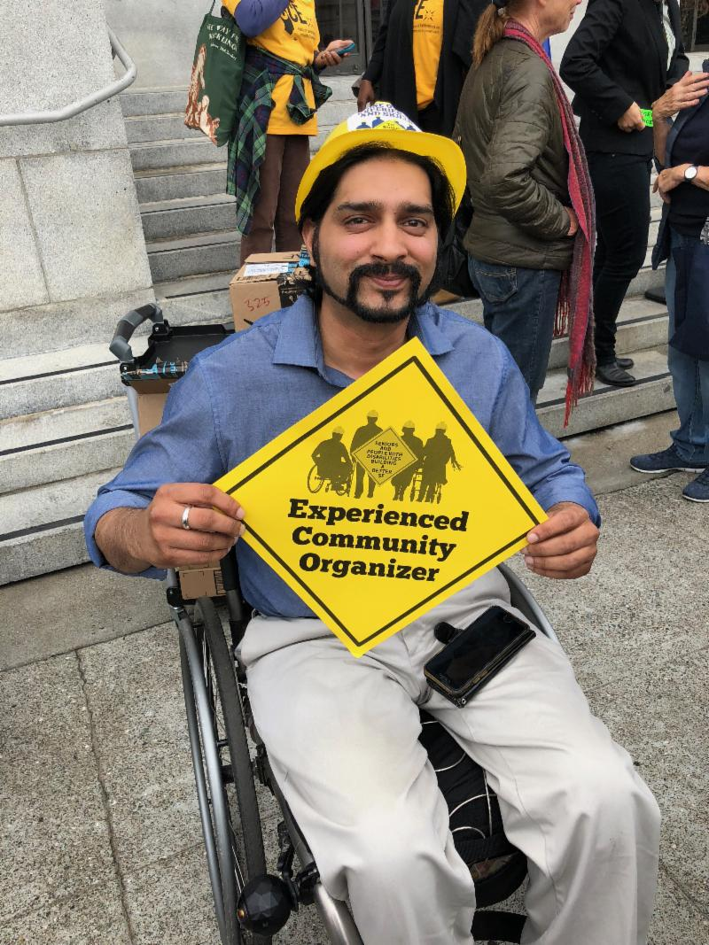 man in a wheelchair with a sign that says Experienced Community Organizer