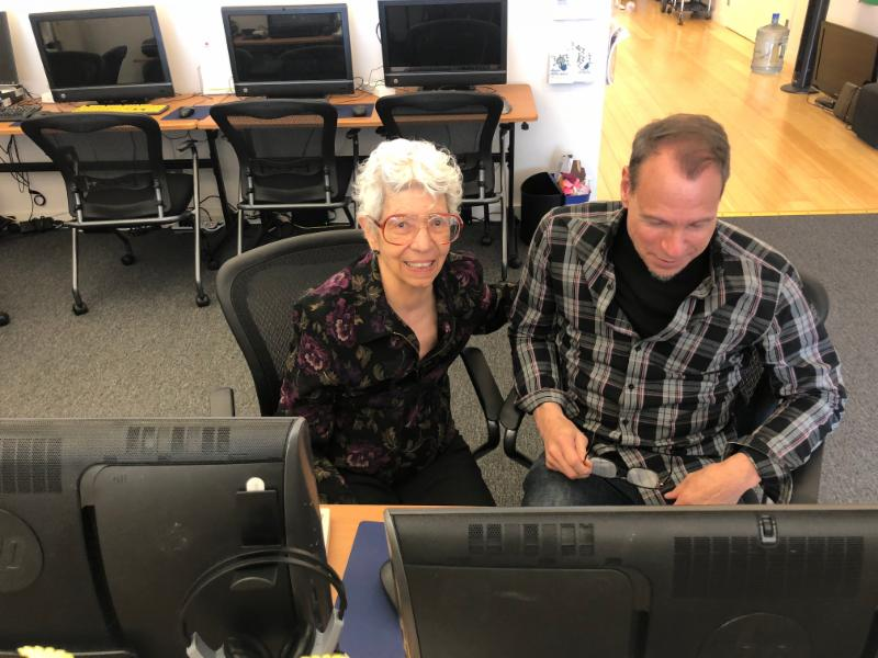 older woman and tutor at the computer