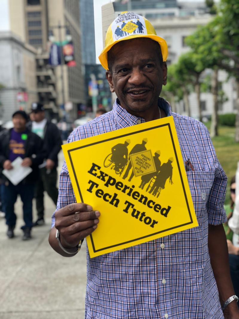 man with a sign that says Experienced Tech Tutor