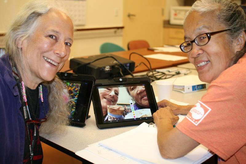 two seniors at computer tablet