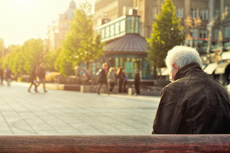 man sitting lonely on a park bench