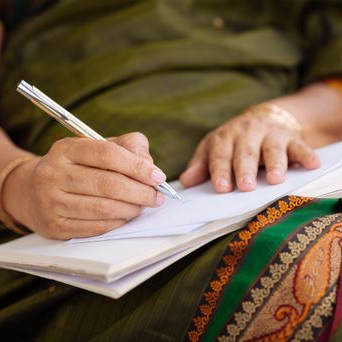 woman writing in a journal on her lap