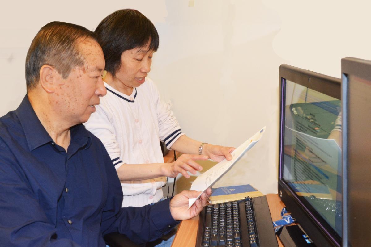 woman tutoring a man at the computer