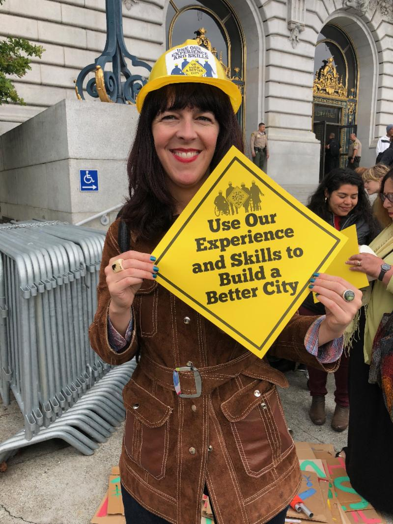 woman with sign that says use or experience and skills to build a better city