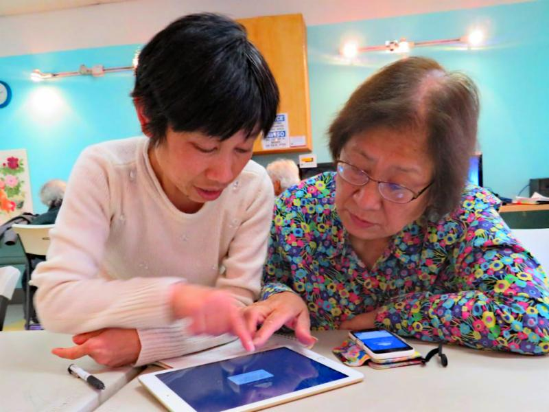 Wanda shows a student how to use her tablet and phone
